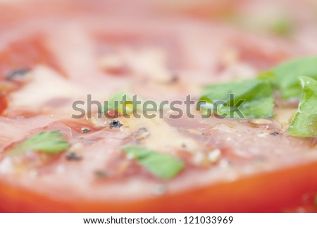 Macro image of slices of Tomato prepared with oilive oil, basil, pepper & salt.