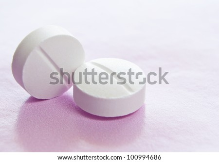 Macro image of two white isolated medicinal tablets.