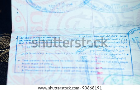 Macro image of visa and immigration stamps in US passport for Dubai or Abu Dhabi in the UAE
