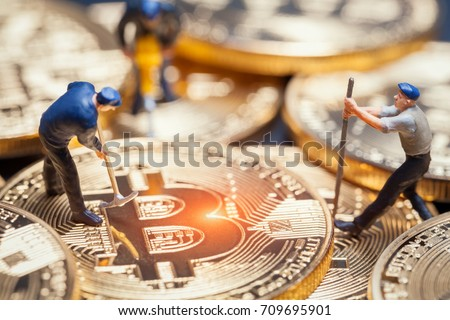 macro miner figures working on group of bitcoins. virtual cryptocurrency mining concept