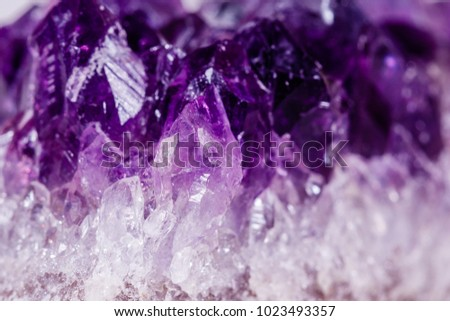 Macro mineral stone purple amethyst in crystals on a white background close up #1023493357