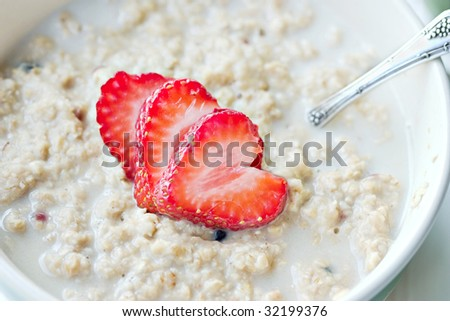 Macro of a bowl of hot oatmeal with fresh strawberries cut into the shapes of hearts for a heart healthy breakfast.