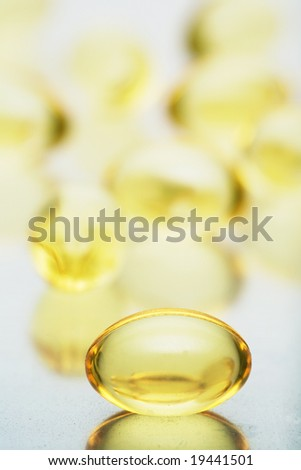 Macro of a bunch of yellow gel pills.