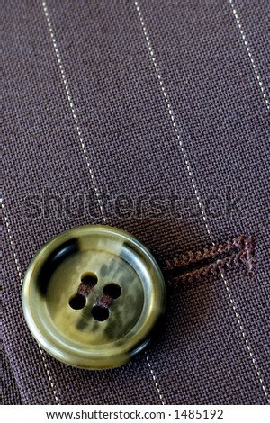Macro of a buttonhole in a businessman's pin-stripe suit. Texture and light.