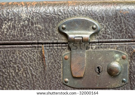 Macro of a locked metal latch of an antique suitcase