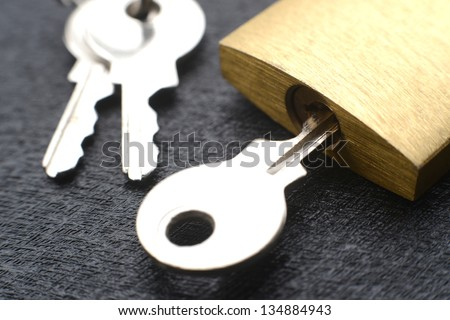 Macro of a locked padlock with the key on it #134884943