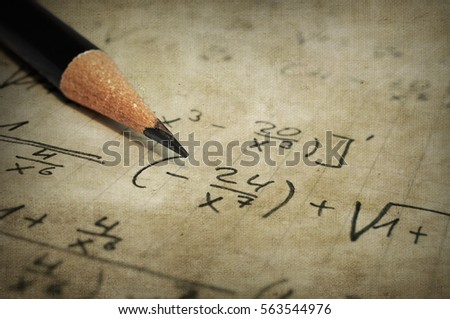 Macro of a old yellowed paper with maths-formulas and a pencil
