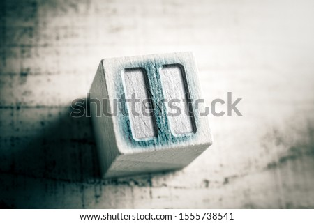 Macro Of A Pause Icon On A Wooden Block On A Table #1555738541