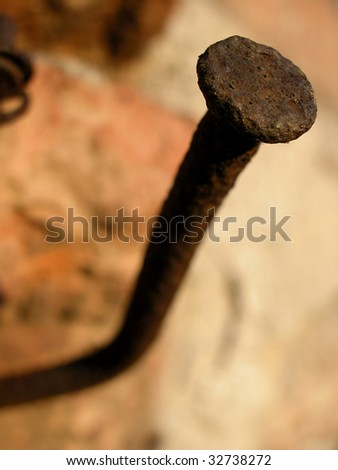 Macro of a rusty old nail in the wall