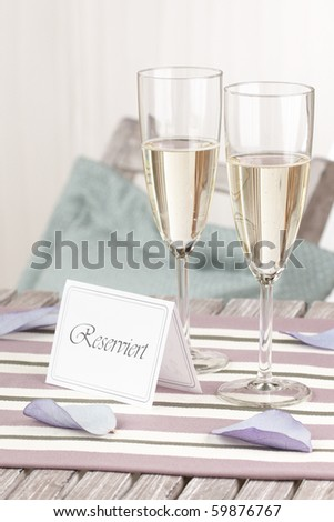 macro of a table with two glass of champagne and a reserved sign