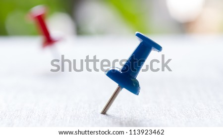 Macro of Blue and red push pins on the wood plane