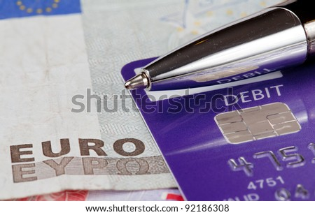 Macro of debit card and pen on top of euro note to illustrate currency crisis in Europe