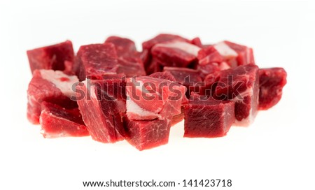 Macro of diced chunks of raw lamb and mutton meat isolated on white