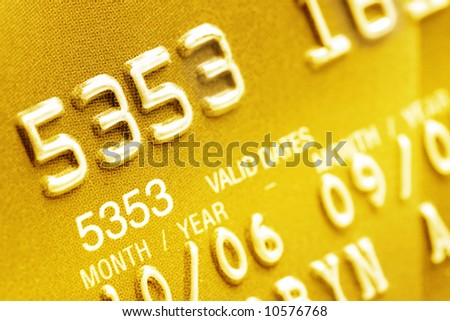 Macro of digits on a gold credit card.