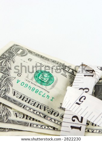 macro of money being tightened by tape measure
