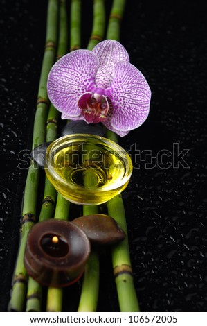 Macro of orchid and bamboo grove,massage oil,candle on black background
