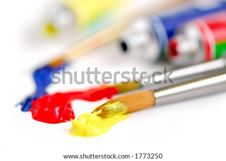 Macro of paintbrushes and paint tubes of primary colors
