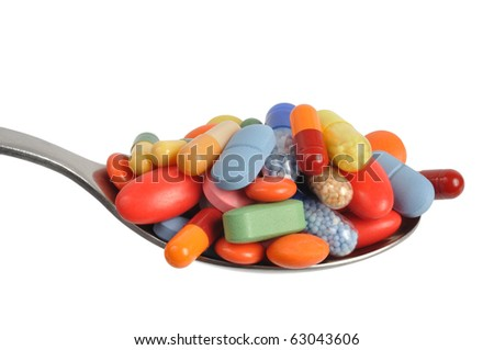 Macro of pills and capsules on a teaspoon isolated on white - stock photo