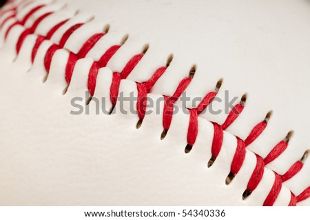 Macro of red stitches on the seam of a white leather baseball