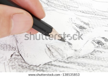 Macro of Sketching a Woman's Face with a Pencil in narrow focus - stock photo