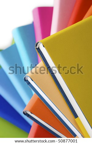 Macro of spiral stack of colorful real books, yellow book on top.