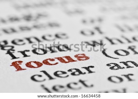 Macro of the word focus in the dictionary, with entire image in black and white apart from the word focus, which is in red
