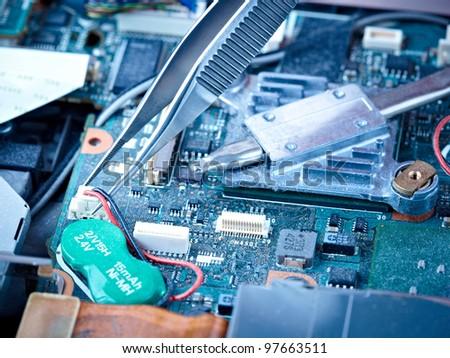 macro of tweezers holding a battery connector