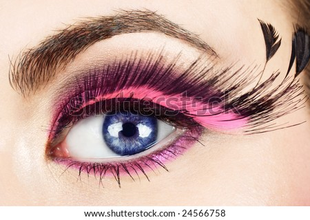 Macro of woman?s eye with long pink feather fake eyelashes