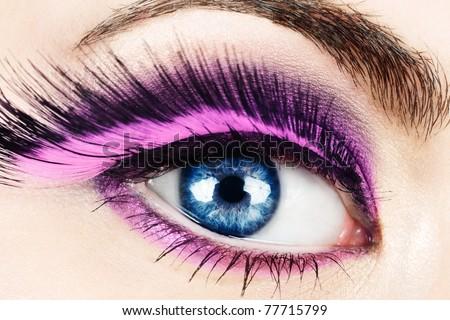 Macro of woman\'s eye with long pink feather fake eyelashes.