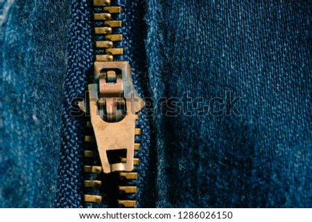 Macro of yellow zipper on blue jeans trousers, selective focus zipper. Royalty high-quality free stock photo image of close up of gold zipper on a blue jean trousers background with space for text #1286026150