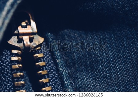Macro of yellow zipper on blue jeans trousers, selective focus zipper. Royalty high-quality free stock photo image of close up of gold zipper on a blue jean trousers background with space for text #1286026165