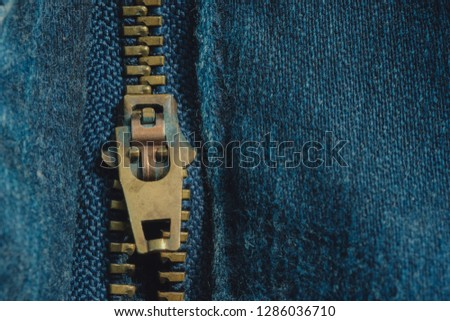 Macro of yellow zipper on blue jeans trousers, selective focus zipper. Royalty high-quality free stock photo image of close up of gold zipper on a blue jean trousers background with space for text  #1286036710