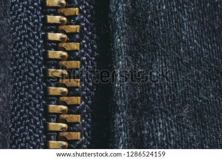 Macro of yellow zipper on blue jeans trousers, selective focus zipper. Royalty high-quality free stock photo image of close up of gold zipper on a blue jean trousers background with space for text #1286524159