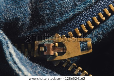 Macro of yellow zipper on blue jeans trousers, selective focus zipper. Royalty high-quality free stock photo image of close up of gold zipper on a blue jean trousers background with space for text #1286524162