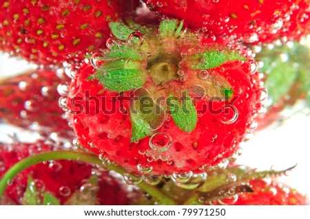 Macro on bubbly strawberry on soda glass
