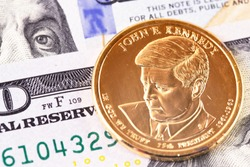 macro one dollar golden coin with John F. Kennedy portrait, and hundred dollars banknotes
