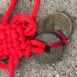 Macro photo Chinese ritual Buddhist charm coins. Background asian ritual Feng Shui coins with red knot good luck. Image of ritual coins with a red thread tied in knots