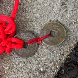 Macro photo Chinese ritual Buddhist charm coins. Background asian ritual feng shui lucky coin with red knot good luck. Image of ritual coins with a red thread tied in knots