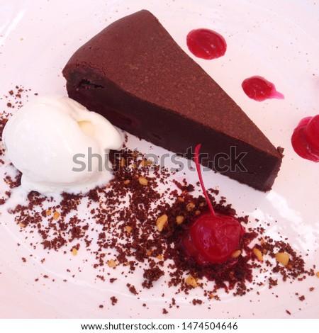 Macro photo chocolate cake with ice cream and cherry. Food product dessert chocolate cake on white plate