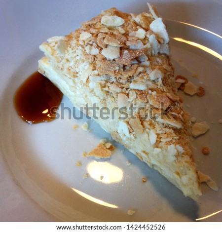 Macro photo food dessert puff cake. Texture background puff cake with nuts and caramel syrup. The image of a piece of puff vanilla cake on a white plate
