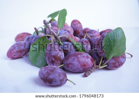 Macro photo food fruit plum on a white background. Texture background of fresh blue plums. Pictures fruit food blue plums