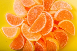 Macro photo multi-colored marmalade jelly candy's. Dessert marmalade in the form of lemon and orange slices. The sweetness of jelly candy yellow and orange. Copy space