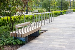 Macro photo of a modern wooden bench in the city park. City improvement, urban planning, public spaces. Wooden garden bench in the city on the background of nature