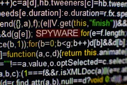 Macro photo of computer screen with program source code and highlighted SPYWARE inscription in the middle. Script on the screen with virus in it. Cyber security concept. Technology background.