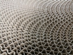 Macro photo of corrugated cardboard roll. Abstract wavy material textured background for industrial issues.