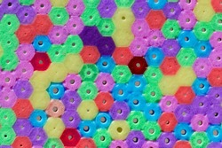 Macro photo of different colored plastic beads as background or texture.