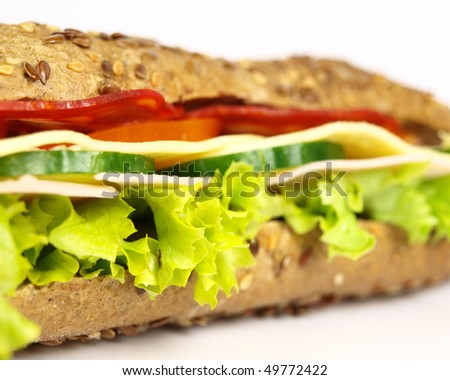 Macro photo of French wholemeal baguette sandwich on white background