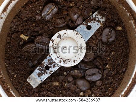 Macro photo of freshly ground coffee in electric coffee grinder.
