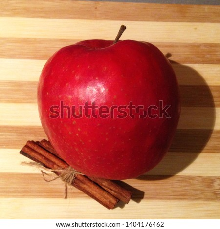Macro photo of nature red apple and cinnamon stick. Background ripe juicy apple and fragrant cinnamon lie on a wooden board.