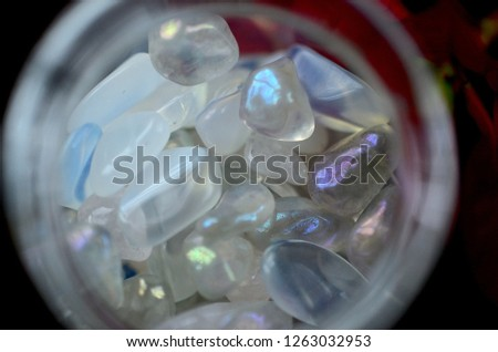 Macro photo of Opalite in glass jar. Rainbow crystal chips in vial. Natural lighting micro lens, healing crystals in pile. Rainbow iridescent crystals in jar.